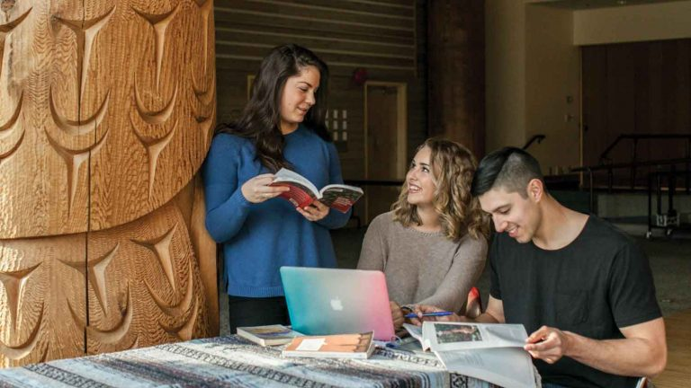 Three students reading books, UBC Aboriginal Student Affairs